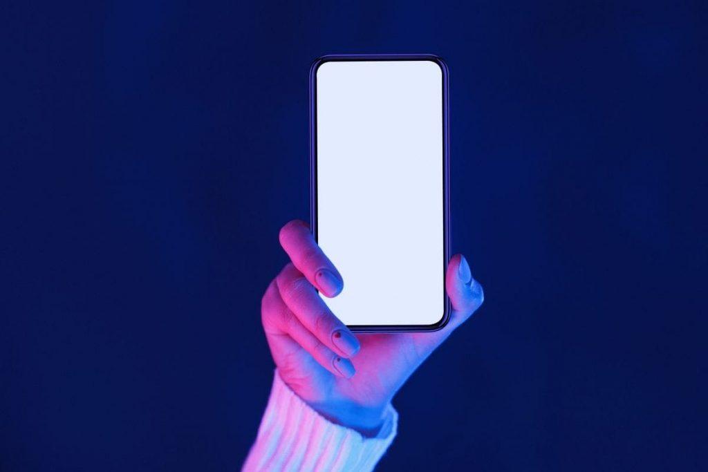 Una persona levantando su celular en blanco haciendo referencia al Minimalismo Digital y la limpieza del contenido